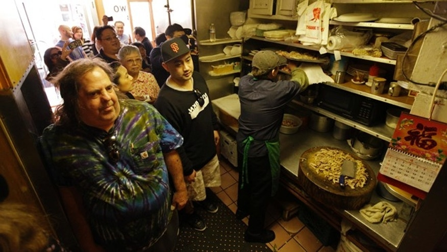 April 20: Sam Begler, left, and other customers wait in the kitchen for a table at the Sam Wo restaurant in Chinatown in San Francisco.