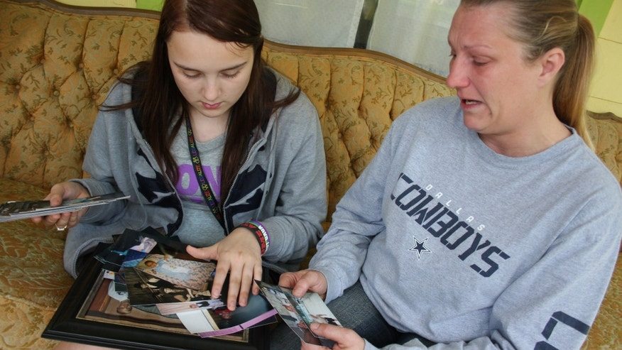 April 17: Kenneth Weishuhn's sister, Kayla Weishuhn, 16, and his mother, Jeannie Chambers, look at photos of Kenneth, 14, who committed suicide Sunday, April 15, 2012, at their home Primghar, Iowa.