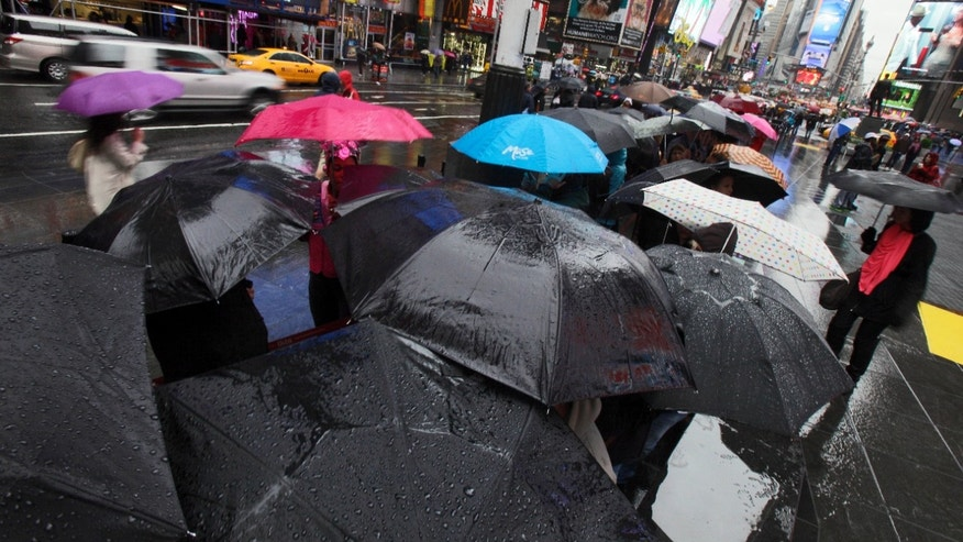 April 22: People use umbrellas for shelter as they wait to buy Broadway theater tickets in New York's Times Square.