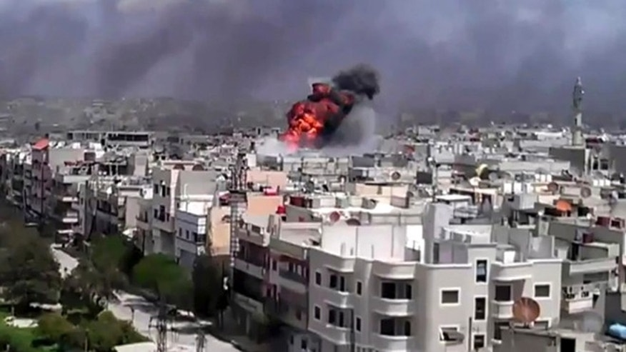 April 20: This image made from amateur video and released by Shaam News Network purports to show an explosion amid heavy shelling in the Khaldiyeh area of Homs, Syria.