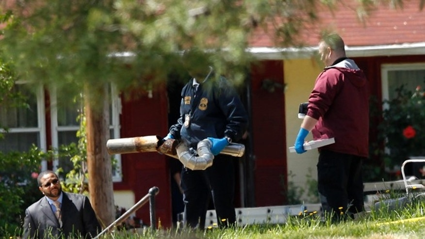 April 24, 2012: Investigators carry a broken exhaust pipe from a home in Oxon Hill. Five people are dead in a Maryland suburb of Washington of suspected carbon monoxide poisoning.