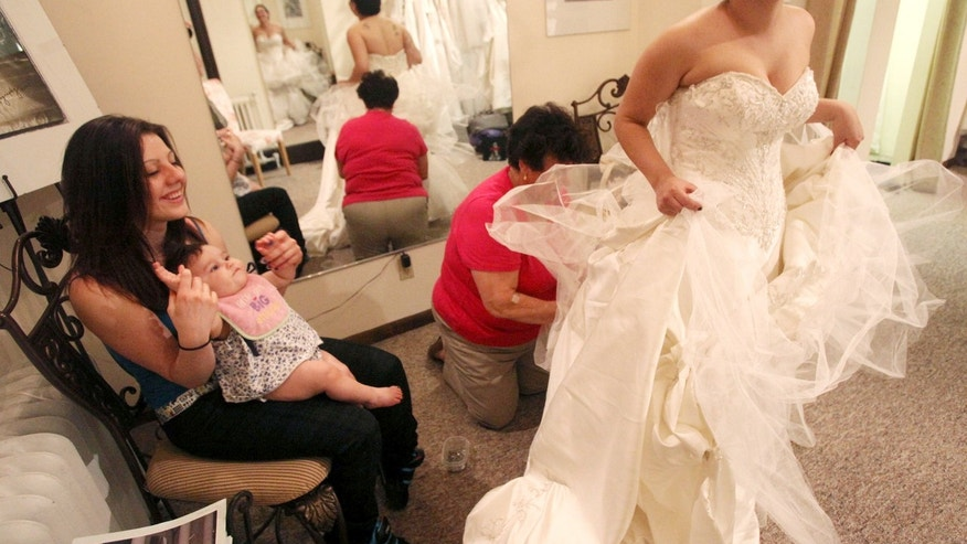 April 8, 2010: Jessica Vega, right, tries on the wedding gown at Bella Coutre, in Newburg, N.Y.