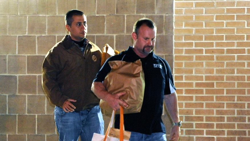 April 22: George Zimmerman, left, walks out of the intake building at the John E. Polk Correctional Facility with a bondsman in Sanford, Fla.