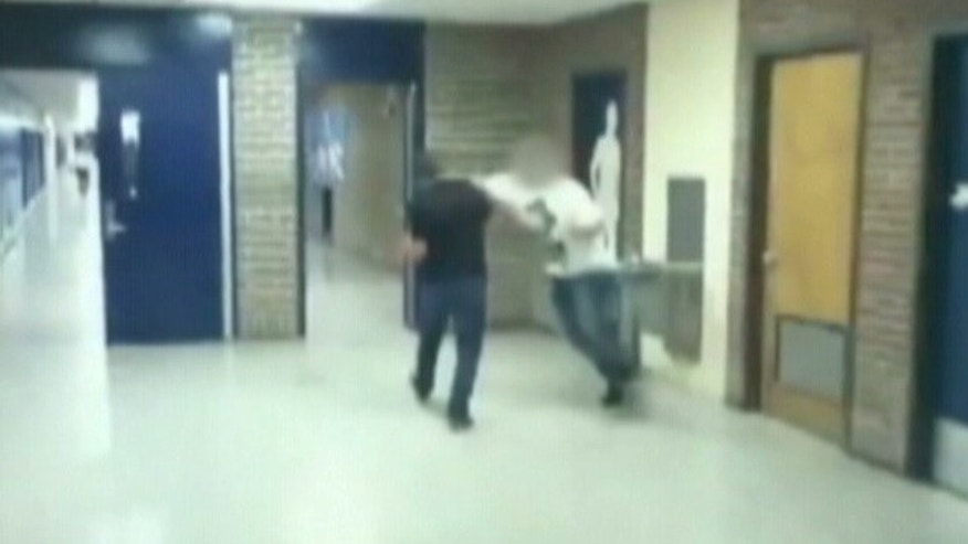 This image, obtained by Fox affiliate WFXT-TV, shows a male student punching a classmate at a Massachusetts high school. Police are investigating the incident after video of the punch surfaced online Thursday.