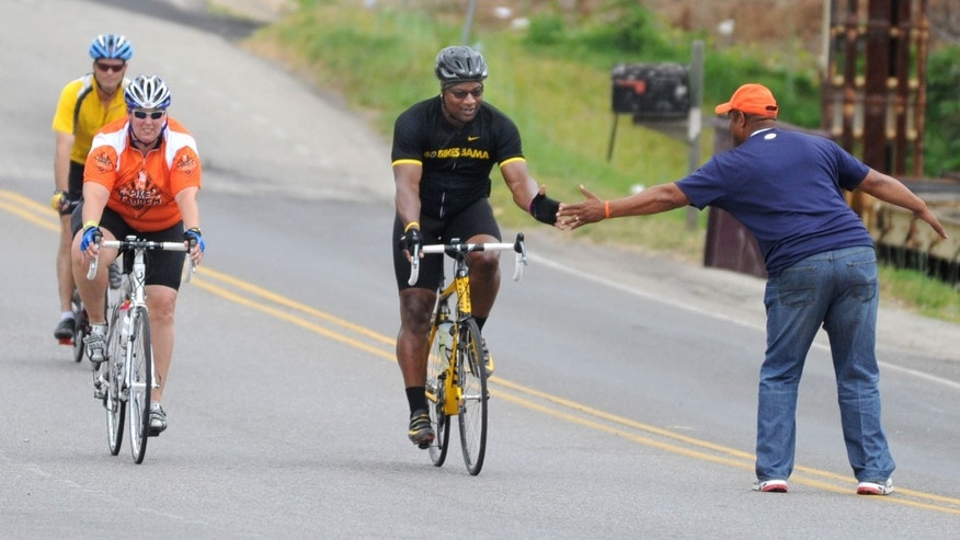 April 27, 2012: Bo Jackson greets a fan as he pedals to Jack's restaurant in Pleasant Grove, Ala.