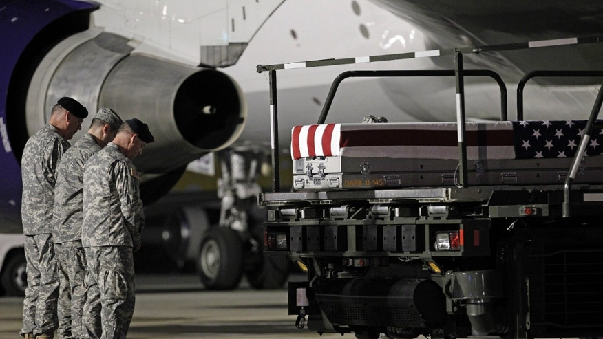 May 3, 2012: Chaplain Col. Dennis Goodwin, left, directs a prayer over the transfer case containing the remains of Army Capt. Bruce K. Clark of Spencerport, N.Y., upon arrival at Dover Air Force Base, Del. The Department of Defense announced the death of Clark who was supporting Operation Enduring Freedom in Afghanistan. (AP)