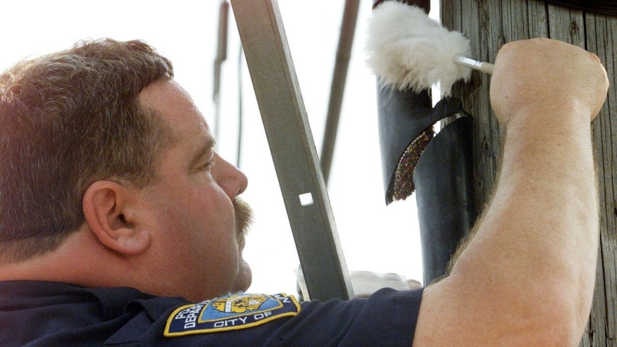 FILE: A New York City police officer dusts a vandalized telephone cable for fingerprints on a service pole in the Bath Beach section of Brooklyn, New York.