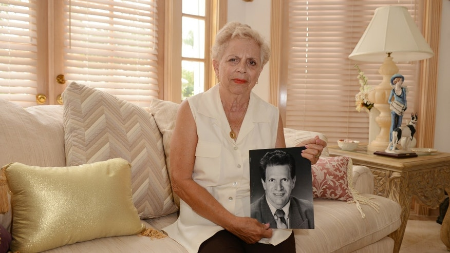 MAY 10: Shirley Lombardo embraces a photo of her brother Jerry Berg who died of lung disease brought on by 9/11 toxic smoke, on May 10, 2012 in Tequesta, Florida.