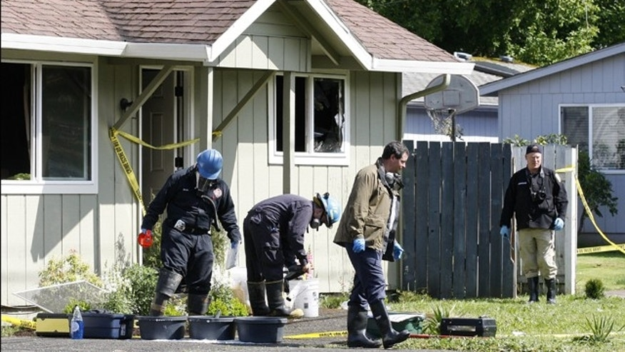 May 22, 2012: Investigators search in the front yard of a home where the bodies of the woman and children were discovered in Salem, Ore.