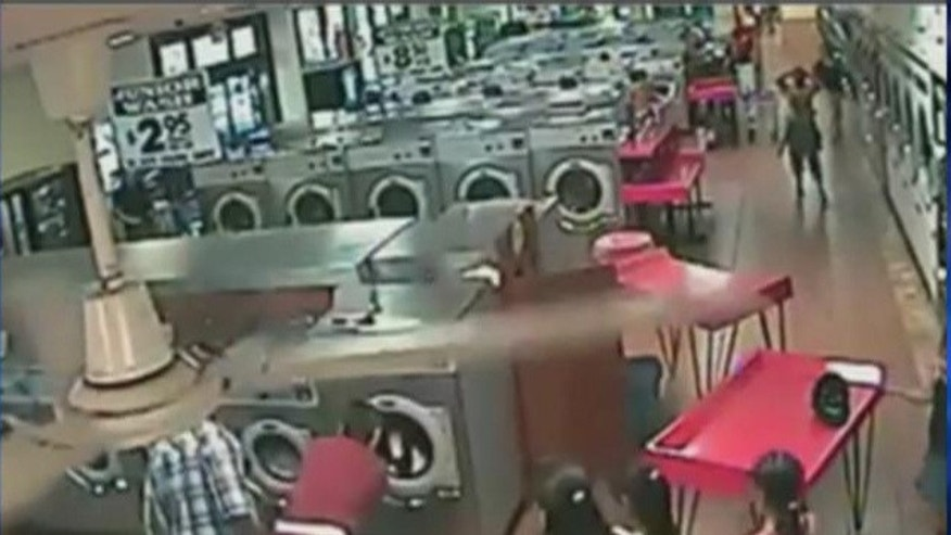 A local laundromat's surveillance video shows a small child loaded into a washing machine.