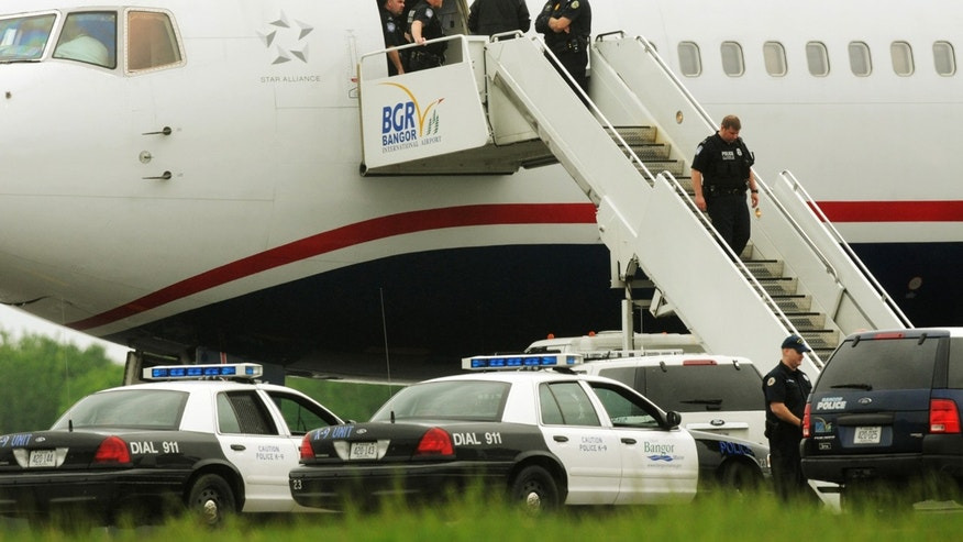May 22, 2012: Law enforcement officials stand on a jet bridge and a passenger jet on the tarmac at Bangor International Airport, in Bangor, Me. The plane was diverted to Maine during its flight from France to Charlotte.