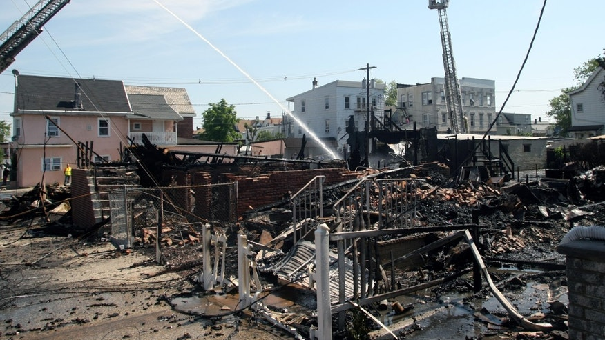 June 3, 2012: Firefighters work at the scene of an early-morning fire in Perth Amboy, N.J. that destroyed four connected homes and seriously injured three people, including an infant.