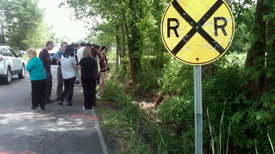 June 3, 2012: People gather at the scene of an early-morning crash on Boston Road in Lorain County, Ohio to pay their respects and mourn three teens who died there.