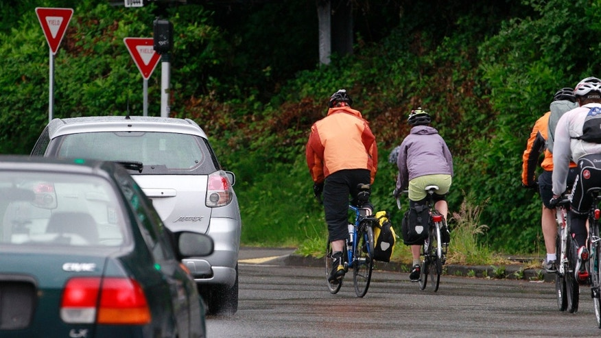 May 31, 2012: Bicyclists commute during the morning rush hour past cars in Seattle.
