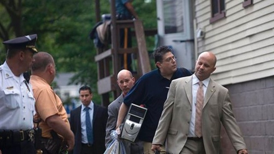June 6, 2012: New York City police detectives carry out items from the home of Pedro Hernandez in Maple Shade, N.J.