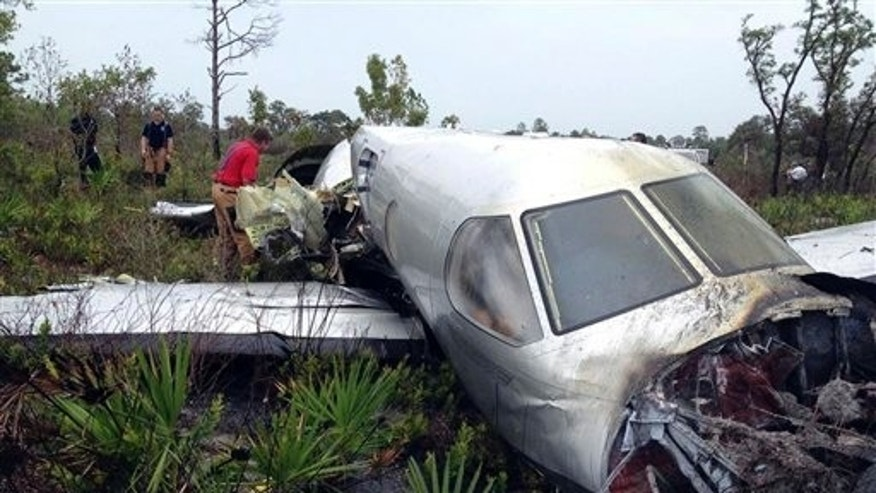 In this photo provided by the Polk County Sheriff's Office, emergency personnel investigate the site where a Pilatus PC-12, a single-engine turboprop passenger plane, crashed near Lake Weohyakapka, aka Lake Walk In the Water, in southeast Polk County, Fla. on Thursday, June 7, 2012. Ronald Bramlage, 45, of Junction City, Kan., who was piloting the plane, his wife Rebecca and their four children were killed in the crash.