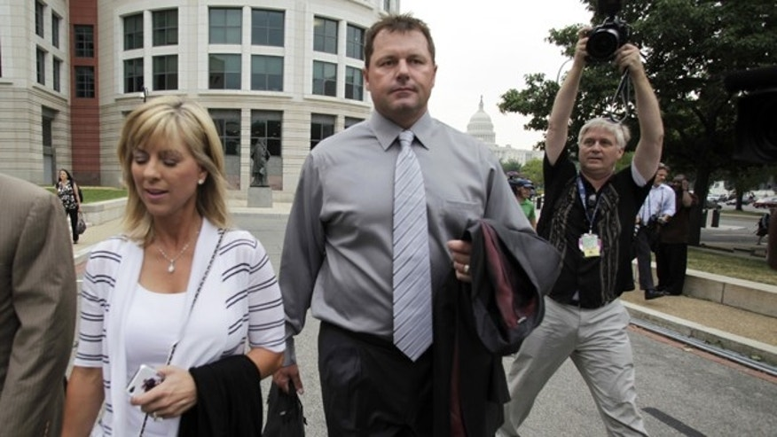 July 6, 2011: Former Major League Baseball pitcher Roger Clemens arrives, with his wife Debbie, for the first day of his perjury trial, at the federal courthouse in Washington.