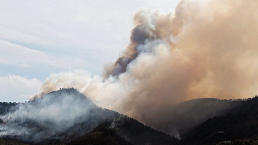 June 11: A plume of smoke rises above the mountain peaks as the High Park wildfire burns west of  Fort Collins, Colorado.