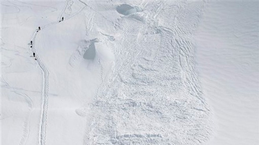 June 15, 2012: In this photo provided by the National Park Service, climbers hike through the area where an avalanche swept a Japanese climbing team off a hill during their descent from Alaska's Mount McKinley.