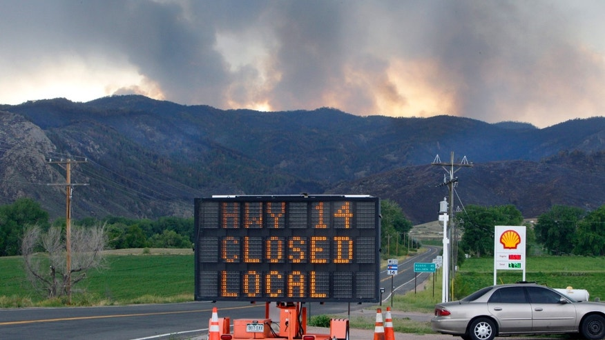June 15, 2012: A sign warns motorist of the closure of Highway 14 through Poudre Canyon as columns of smoke rise in the distance from the High Park wildfire west of Fort Collins, Colo.