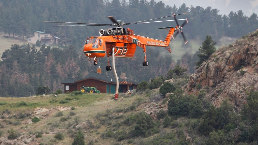 June 15, 2012: A Erickson Air Crane firefighting helicopter flys to a pond to refill its tank while fighting  the High Park wildfire, west of Fort Collins, Colo.