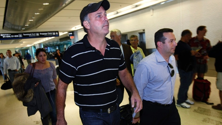 Nov. 30, 2011: Gary Giordano, center, a Maryland businessman who had been jailed in Aruba on suspicion of involvement in the presumed death of his traveling companion, walks through Miami International Airport in Miami with attorney Jose Baez.