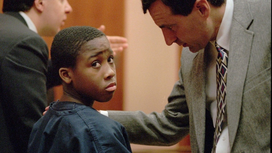 Feb. 11, 1998: Nathaniel Jamal Abraham, 12, of Pontiac, Mich., listens to his attorney in Juvenile court.  Abraham, who committed murder at age 11, has been sentenced to five years of probation in a prison guard assault case.
