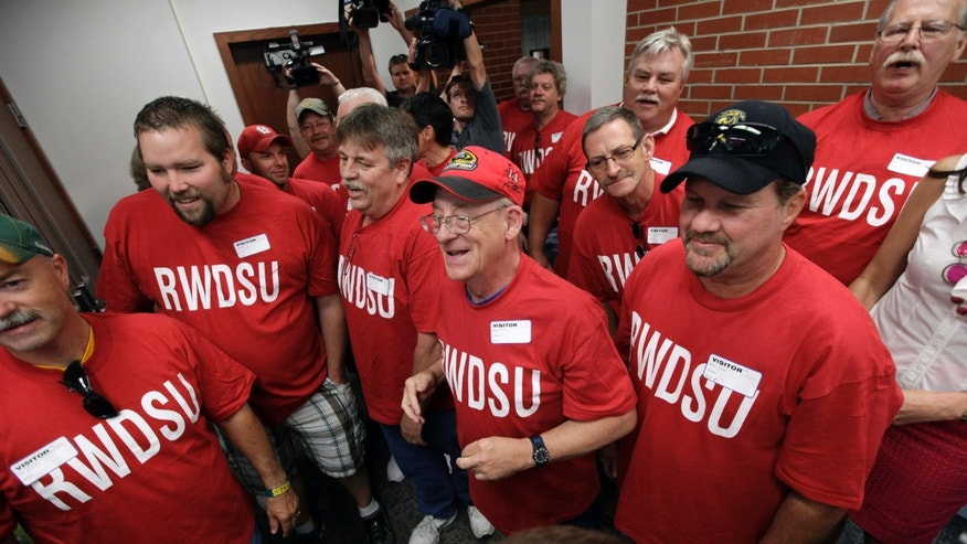 June 20, 2012: Workers from the Quaker Oats plant in Cedar Rapids, Iowa, look on as their winning $241 million Powerball ticket is scanned at the Iowa Lottery headquarters in Des Moines, Iowa.