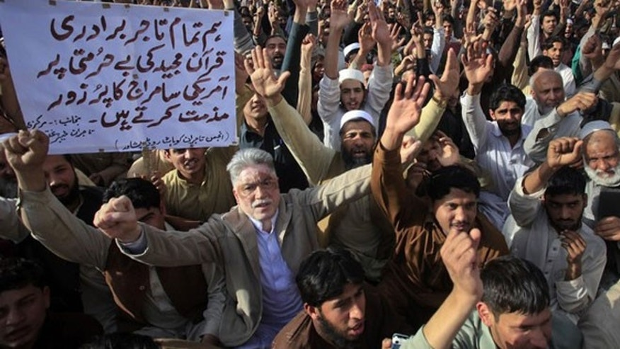 March 6, 2012: Traders hold placards as they shout anti-U.S. slogans during a demonstration in Peshawar. About 200 protesters gathered to condemn the February 21 burning of copies of the Koran at NATO's main base in Afghanistan.