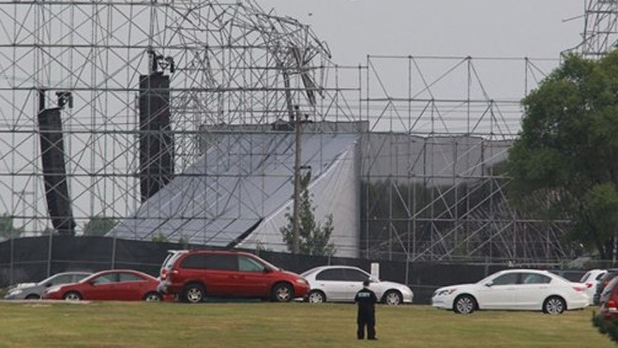 June 16, 2012: A security guard surveys the scene near a collapsed concert stage at Downsview Park in Toronto.