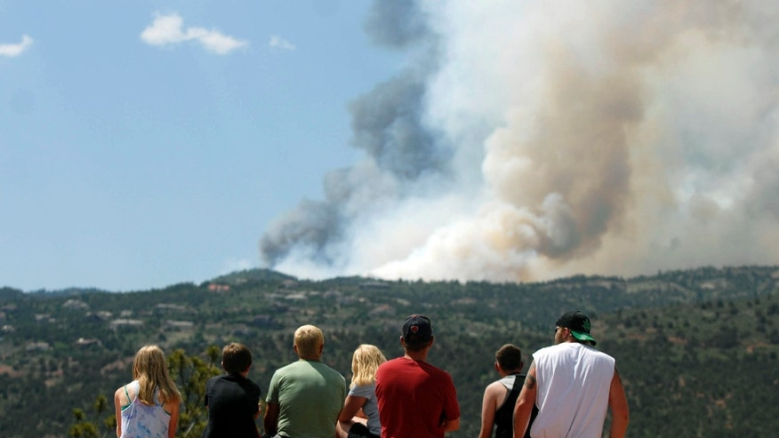 June 23: People watch as smoke billows from a wildfire west of Colorado Springs, Colo..