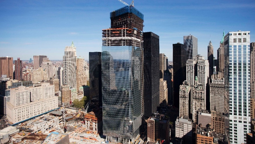 In a April 17, 2012 photo, Four World Trade Center, center, rises above the World Trade Center construction site, in New York.