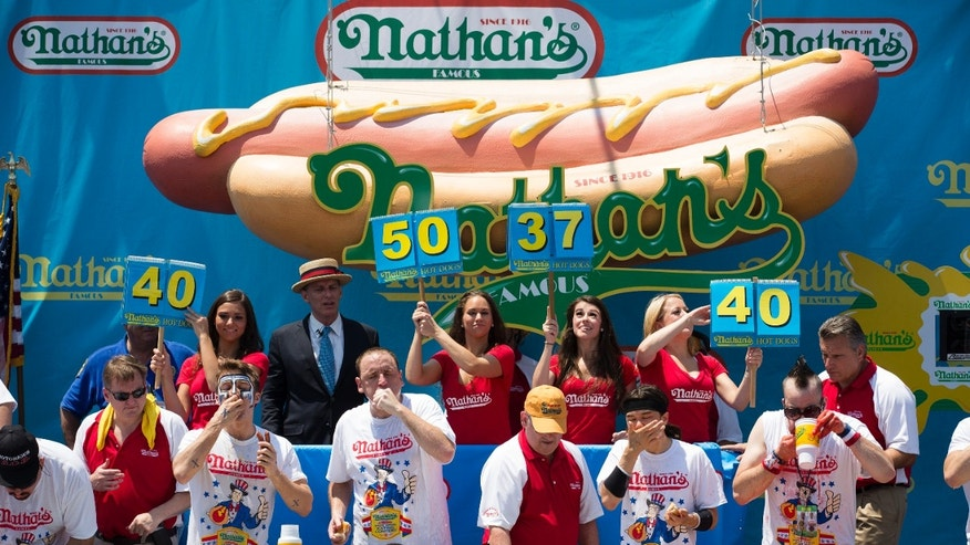 Five-time reigning champion Joey Chestnut, second competitor from left, competes in his sixth Nathan's Famous Hot Dog Eating World Championship, Wednesday, July 4, 2012, in the Brooklyn borough of New York. Chestnut tied his personal best and the record with eating 68 hot dogs. Last year, Chestnut won with 62 hot dogs. (AP Photo/John Minchillo)