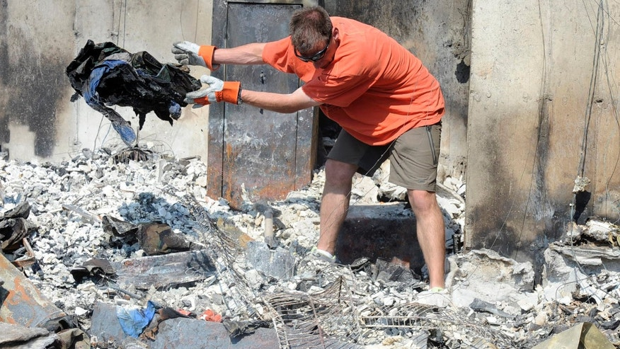 July 5, 2012: Dr. Ted Stefani digs through to salvage items from the remains of his home in the Mountain Shadows neighborhood of Colorado Springs, Colo.
