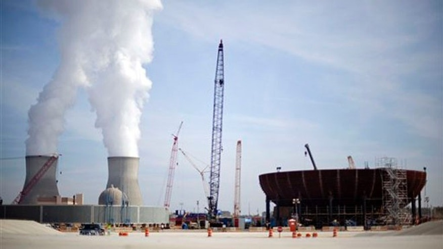 Feb. 15, 2012: In this file photo, cooling towers for units 1 and 2 are seen at left as the new reactor vessel bottom head for unit 3 stands under construction at right at the Vogtle nuclear power plant in Waynesboro, Ga.