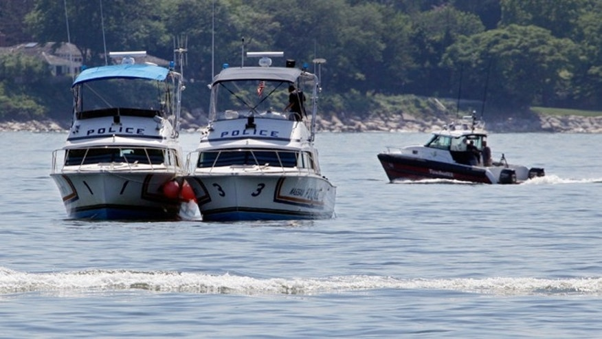 July 6: Two Nassau County police boats are stationed near the opening to the Long Island Sound in Lloyd Harbor, N.Y.