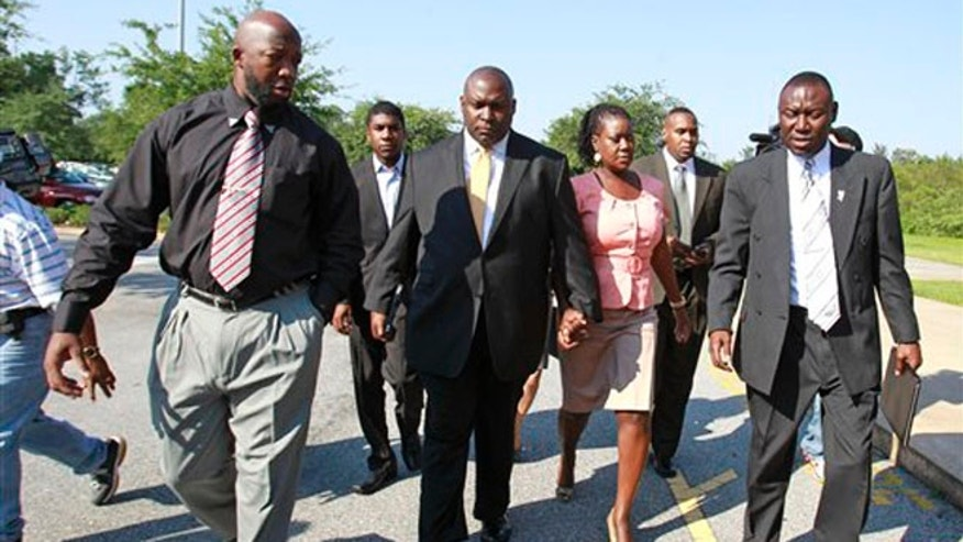 June 29, 2012: Tracy Martin, far left, father of Trayvon Martin; Jahvaris Fulton, second from left, brother of Trayvon Martin; attorney Daryl Parks, center, Sybrina Fulton, mother of Trayvon Martin and attorney Benjamin Crump, far far right, arrive at the Seminole County  Criminal Justice Center to attend a bond hearing for George Zimmerman in Sanford, Fla.