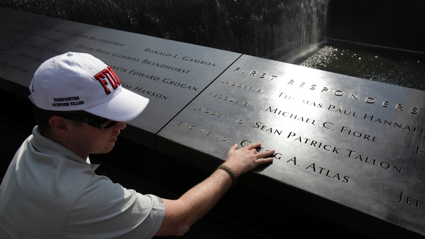 July 4- US Army PFC Kyle Hockenberry of Marietta, Ohio, touches the name of a first responder etched in the 9/11 Memorial at ground zero in New York.