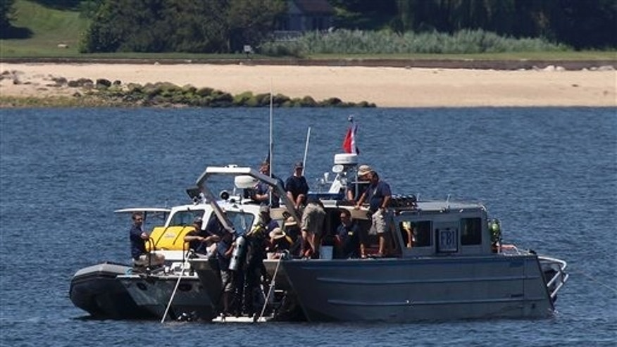 July 10, 2012: Divers leave the water and come up onto an FBI boat over the site of a sunken yacht near Lloyd Harbor, N.Y.