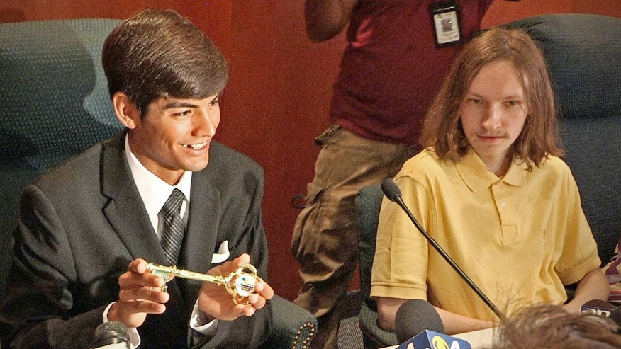 July 9, 2012: Fired lifeguard Tomas Lopez left, smiles while sitting next to Maksim Samartsev, whom he helped rescue on the beach July 2, as the City of Hallandale Beach, Fla., presented him and another rescuer with the key to the city