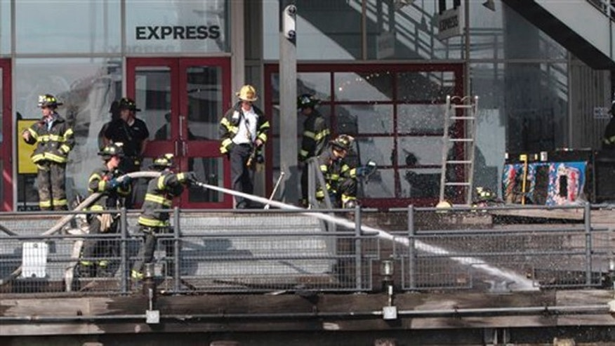 July 14, 2012: Firefighters work to extinguish a fire at PIer 17 in New York.