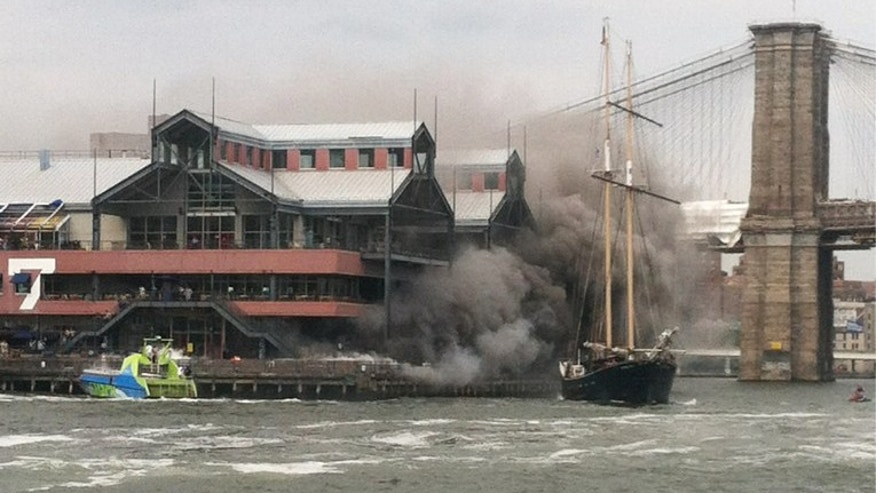 July 14, 2012: This photo provided by Kieran Carley, a New York Water Taxi crew member on the Ikea shuttle, shows plumes of smoke rising from Pier 17 at the South Street Seaport in New York.