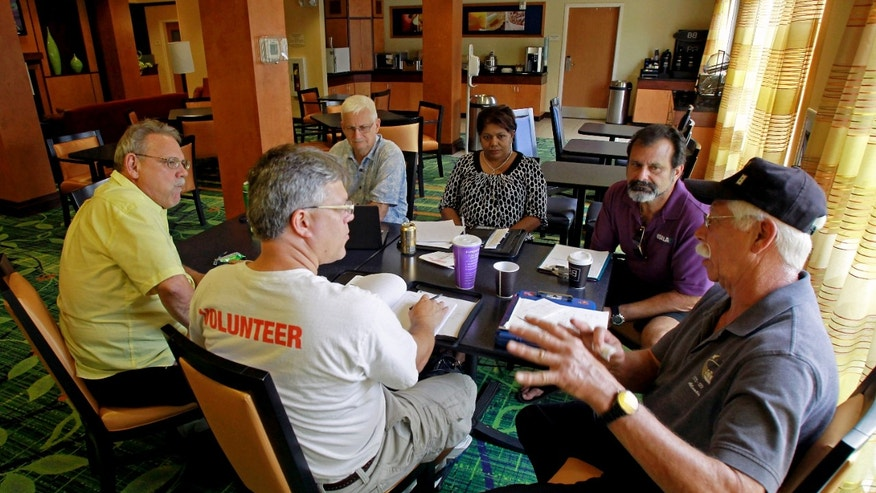 July 11, 2012: Terry White, far right, leads a discussion during a business development meeting of former space workers, clockwise from center, John Hoog, Raymond Steele, Kenneth Mark Higginson Jr., Kay Sunderland and Kevin Harrington, in Titusville, Fla.