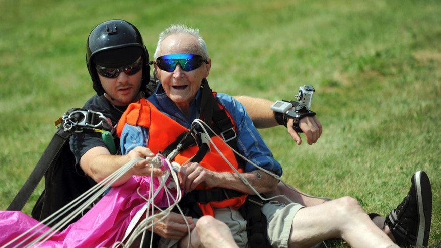 July 15, 2012: 90-year-old Lester Slate, right, of Exeter, Maine, sits on the ground after his first skydiving jump made in tandem with instructor Matt Riendeau, left, at Central Maine Skydiving in Pittsfield, Maine.