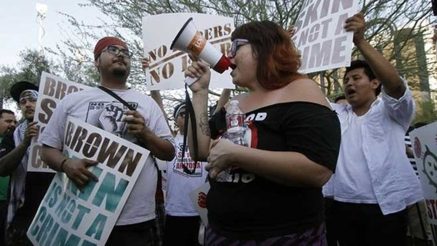 June 25, 2012: People hold signs as they gather during a protest in front of the Immigration and Customs Enforcement offices in Phoenix, Arizona.