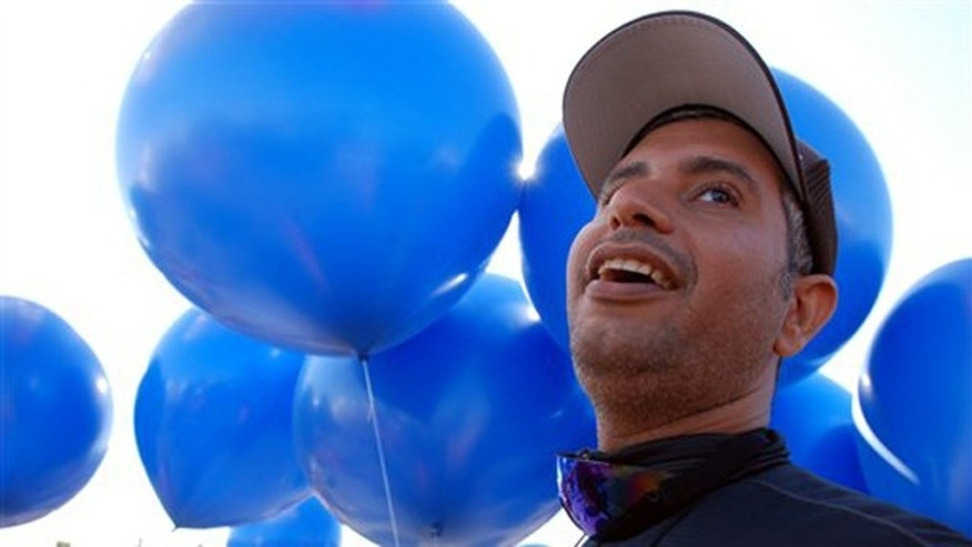 July 14, 2012: Iraqi adventurer Fareed Lafta watches with delight as party balloons are flated with helium to carry him aloft in a tandem lawn chair rig with gas station owner Kent Couch in Bend, Ore..