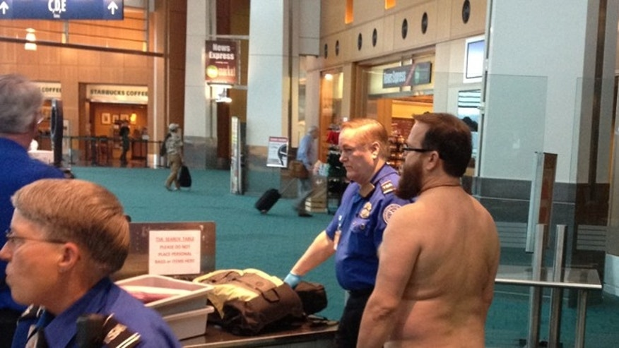 April 17, 2012: In this file photo taken at Portland International Airport, shows John E. Brennan standing naked after he stripped down while going through a security screening area, as a protest against airport security procedures.