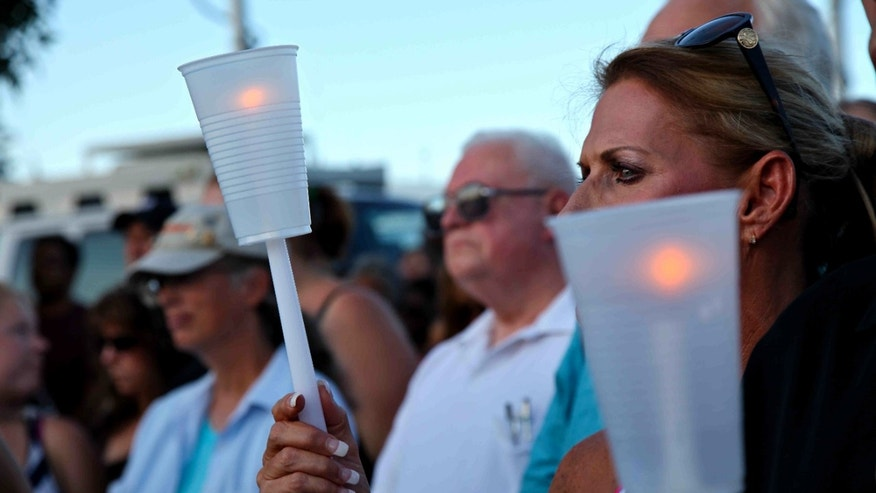 July 20, 2012: Less than 24 hours after 12 people were killed and dozens shot, Alicia Pervette stands across the street, holding a candle in memorial of the victims in Aurora, Colo.