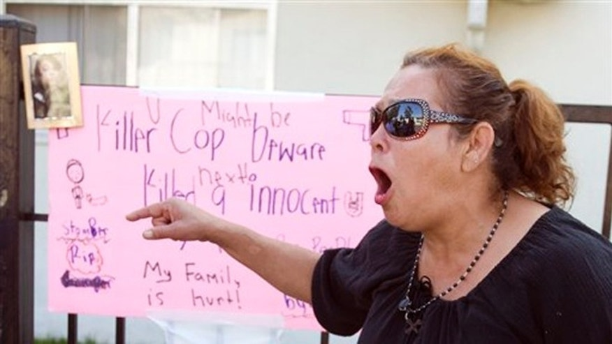 "July 23, 2012: Maria, who wouldn't give her last name because she said she fears the police, shouts ""no mas"", at a memorial on Anna Drive in Anaheim, Calif. for Manuel Angel Diaz, 25, of Santa Ana."