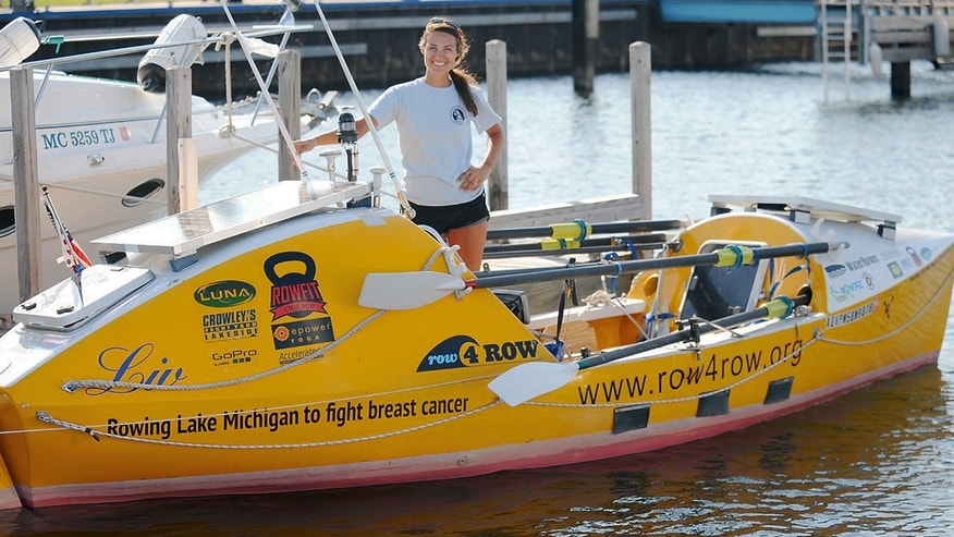 July 12, 2012: Jenn Gibbons poses with her 19-foot ocean rowing boat at a marina in Menominee, Mich.
